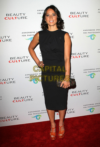 OLIVIA MUNN .at The opening of Beauty Culture - a photographic exploration of how feminine beauty is defined, challenged and revered in modern society held at Annenberg Space for Photography in Century City, California, USA,.May 19th 11..full length black dress sleeveless hand on hip clutch bag  brown tan ysl tribute sandals platform shoes .CAP/ADM/KB.©Kevan Brooks/AdMedia/Capital Pictures.