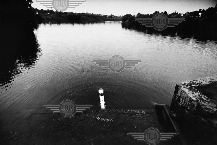 A man dives into an artificial lake next to a coal mine in the Dombas region.