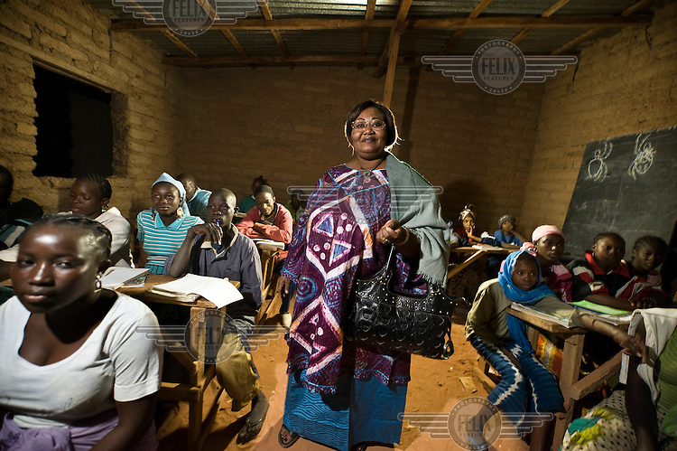 Madame Maiga Kady Baby, director of a local NGO supported by Oxfam Novib, visiting an adult literacy class held at night. A bulb on a car battery provides the light.