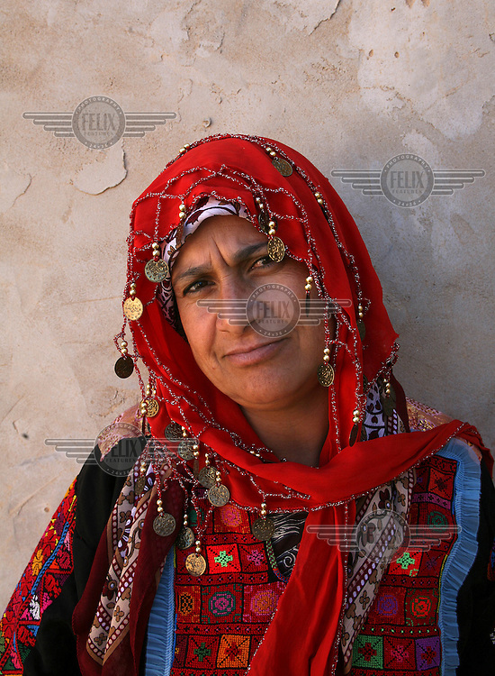 A woman outside her home in the unrecognised Bedouin village of Al Zarnock in the Negev desert. Around 75,000 Bedouin people who live in this region are in unrecognised villages. The villages are not acknowledged by the state of Israel, and lack basic infrastructure, nor do they appear on any offical maps of the country.