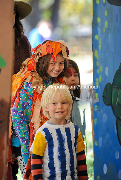 WOODBURY, CT-13 OCTOBER 2012--10132JS04-- August McLeran, 5, of Woodbury and Annika Hughes, 9, of Southbury peek out from behind painted scenes as they wait to come out during a play about Australia on Saturday during the 50 Years of Flanders: Autumn Fest at the Flanders Nature Center in Woodbury. MeLeran was dressed to represent a zebra fish while Hughes was playing a lion fish. .Jim Shannon Republican-American