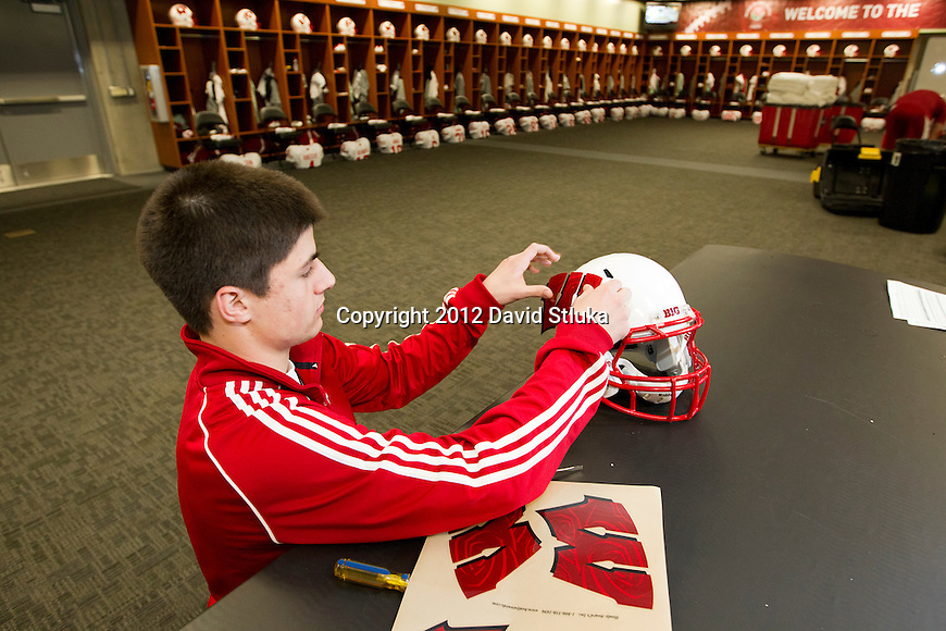 Wisconsin Badgers student manager Alex Graf puts on the Motion W log on a football helmet in the team locker room prior to the 2012 Rose Bowl NCAA football game against the Oregon Ducks in Pasadena, California on January 2, 2012. The Ducks won 45-38. (Photo by David Stluka)