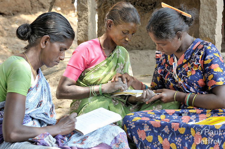 Angali (right) helps Kaniamma (center) with writing during a women's literacy class in Nandambakkam, a tribal village in the southern India state of Tamil Nadu.