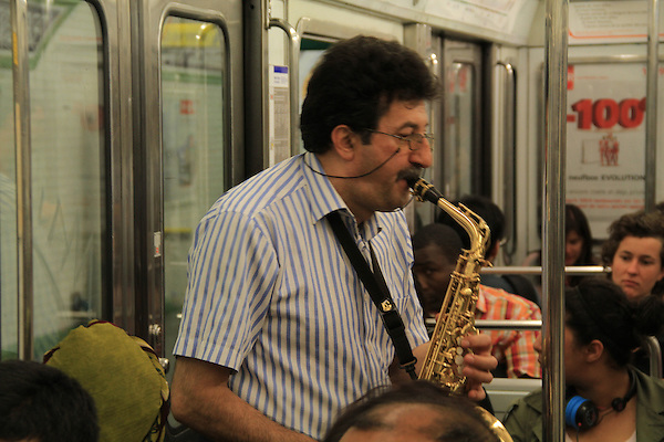 France, Paris. Street Photography.<br /> Think of what you're going to do, before you stand up and take the shot. Determine focal length, exposure and focus. Afterwards, a tip is in order. Saxophonist on the Paris Metro.