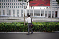 """CHINA. Beijing. A man looks at an advertisement. In recent years construction has boomed in Beijing as a result of the country's widespread economic growth and the awarding of the 2008 Summer Olympics to the city. For Beijing's residents however, it seems as their city is continually under construction with old neighborhoods regularly being razed and new apartments, office blocks and sports venues appearing in their place. A new Beijing has been promised to the people to act as a showcase to the world for the 'new' China. Beijing's residents have been waiting for this promised change for years and are still waiting, asking the question """"Where's the new Beijing?!"""". 2008."""