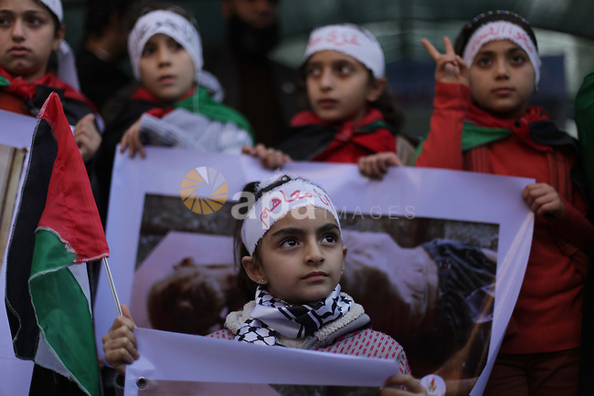 Palestinian Children hold banners during a protest in solidarity with Palestinian children at Yarmouk refugee camp, in front of the Palestinian Red Cross, in Gaza City on Jan. 04, 2013. Palestinian president Mahmoud Abbas ordered Saturday dispatch of immediate food supplies to Yarmouk refugee camp in Syria due to the difficult situation the camp is going through. Photo by Ashraf Amra