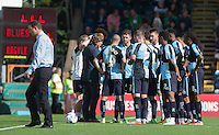 Kick Off is delayed by 6 minutes as Derek Adams manager of Plymouth Argyle talks to Referee Tim Robinson to get clarification the Wycombe players are allowed to wear GPS vests under their kit, which he was worried may be dangerous during the Sky Bet League 2 match between Wycombe Wanderers and Plymouth Argyle at Adams Park, High Wycombe, England on 12 September 2015. Photo by Andy Rowland.