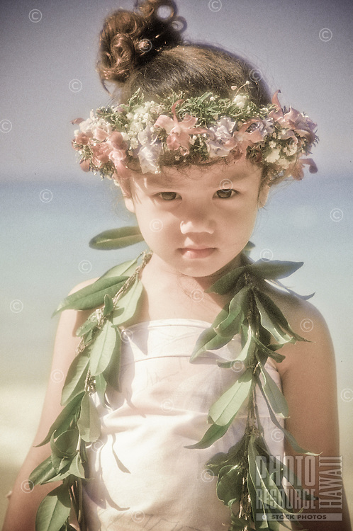 A small child wearing a haku lei and maile at a beach on Oahu.