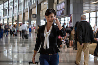 Young business woman with cell phone and luggage in hand at the Couple walking through the Austin–Bergstrom International Airport (ABIA) terminal - Stock Image.
