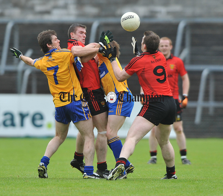 Mark Tubridy and John Hayes of Clare in action against Liam Doyle and Calum King of Down during their senior football championship qualifier game at Cusack Park. Photograph by John Kelly.