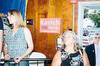 People watch as Republican presidential candidate and Ohio governor John Kasich speak with members of the audience and the media after a town hall campaign event at the Derry VFW in Derry, New Hampshire.