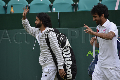 22.06.2013. Stoke park, Slouogh, berkshire, England. The Boodles Challenge mens doubles finals. Jamie Delgado of Great Britain and his American partner James Cerrentani versus the pairing of Adil Shamasolin and Rameez Junaid.<br /> Adil Shamasolin and Rameez Junaid enter the court