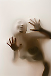 Partially silhouetted nude woman behind translucent fabric