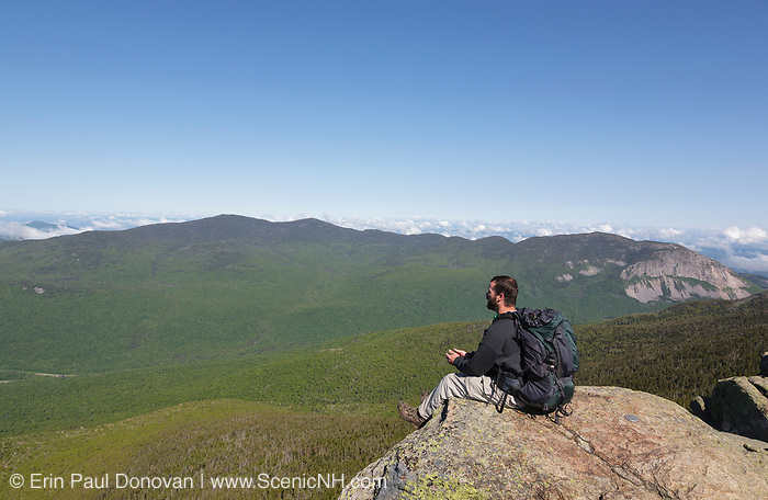 A hiker enjoys the views from the summit of Mount Liberty during the summer months. Located in the White Mountains, New Hampshire USA.