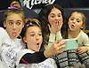 Matison Kindelmann, 6, center, and sister Charlotte Kindelmann, 4, have fun taking 'selfies' with Cold Spring Harbor gymnasts Skylar Basso, second from left (holding phone) and Skye Schlanger during the eight-team Cartwheel for a Cure gymnastics meet at Cold Spring Harbor High School on Monday, Jan. 16, 2017. The sisters were born with cystic fibrosis. Their mother, Teri Kindelmann, is the school's gymnastics head coach.