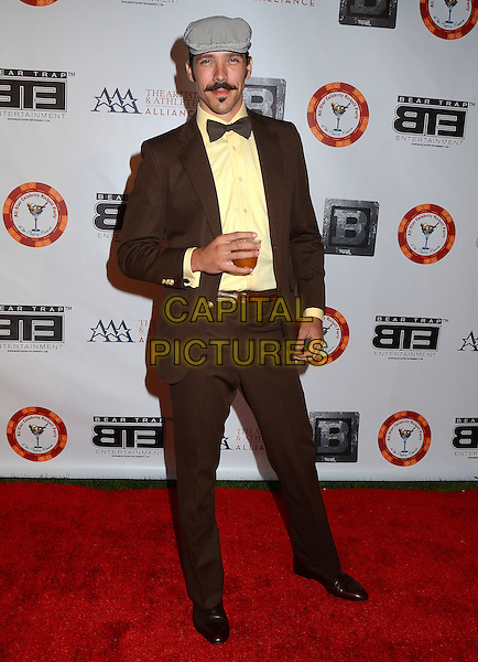 Phoenix Mandoza<br /> 8th Annual BTE All-Star Celebrity Kick-Off Party at Playboy Mansion in Los Angeles, CA., USA.<br /> July 15th, 2013<br /> full length brown suit tuxedo grey gray flat cap hat drink beverage yellow shirt bow tie moustache mustache facial hair<br /> CAP/ADM/BT<br /> &copy;Birdie Thompson/AdMedia/Capital Pictures