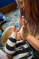 A mother breastfeeds her two year old daughter while doing a high five with her hand with him.<br /> <br /> Lancashire, England, UK<br /> <br /> Date Taken:<br /> 07-01-2015<br /> <br /> &copy; Paul Carter / wdiip.co.uk