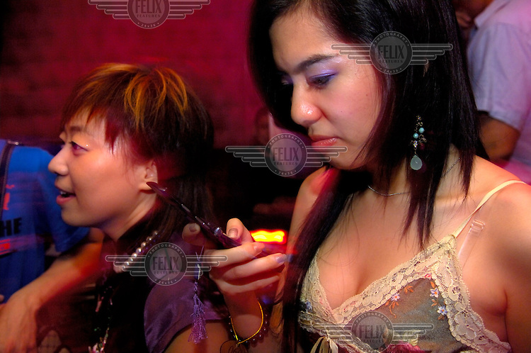 A young woman consulting her mobile phone in a Beijing nightclub.