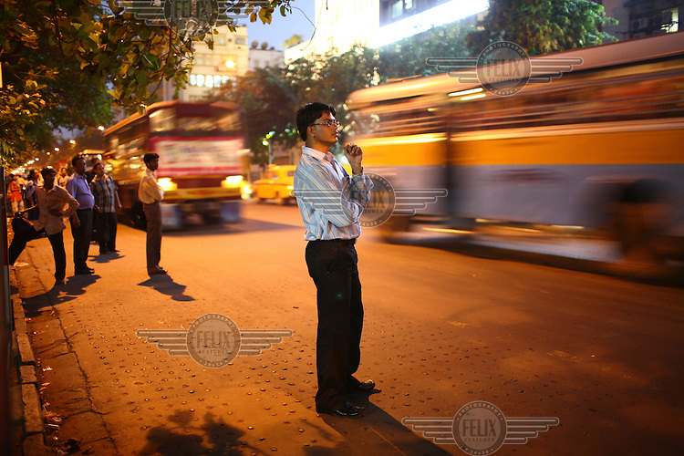 People wait to catch a public bus in Kolkata.