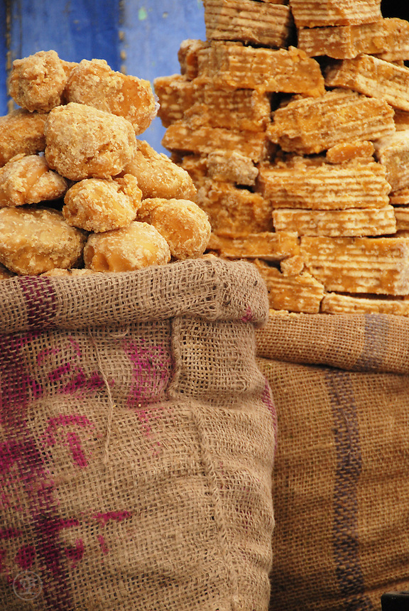 Burlap bags are piled high with jaggery against the blue walls of Jodhpur, Rajasthan, India