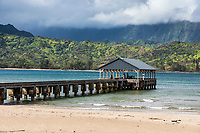 Hanalei Pier, Beach and Bay, backed by lush mountains topped by clouds, northern Kaua'i.