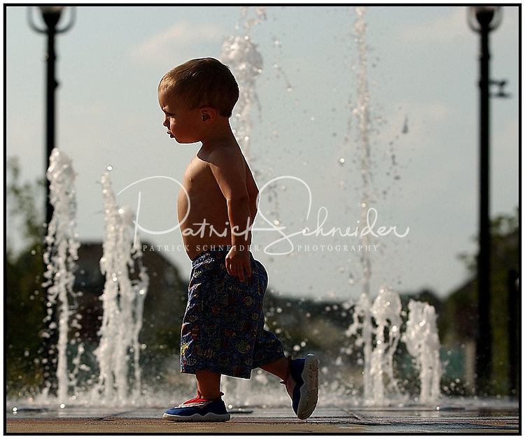 A young boy struts beside water spraying up at a community water park. Image is model released.