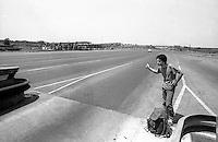 Autostoppista chiede un passaggio  alle auto al casello dell'autostrada A1  all'uscita da Roma (1984)