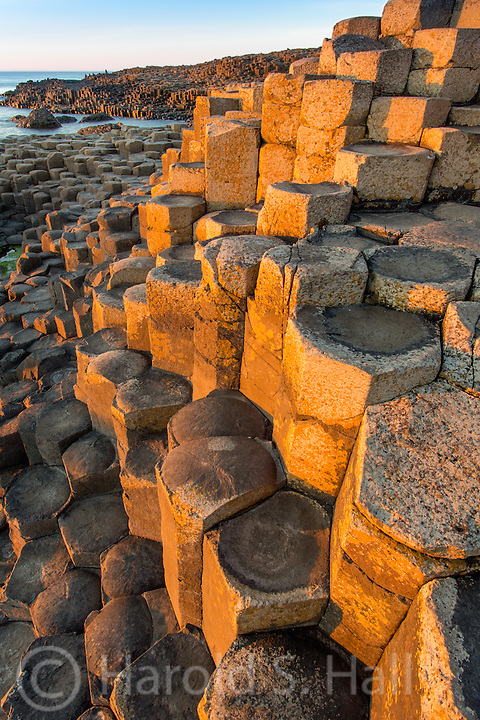 The Giant's Causeway in Northern Ireland dispalys approximately 40,000 interlocking basalt columns, the result of an ancient volcanic eruption. These columns can be jet black in the evening after a rain or golden in the more rare afternoon sun. On sunny days like this one, hundreds of people are crawling around the rocks.