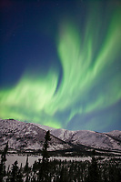 Aurora borealis arcs across the sky over the Brooks mountains at Grayling Lake, Arctic, Alaska