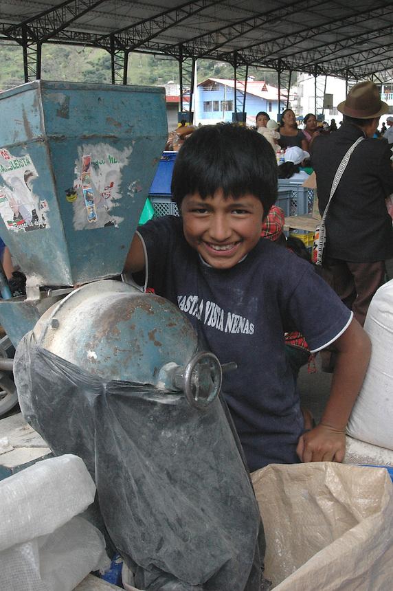 Young boy milling corn flour at outdoor market in Banos, Ecuador