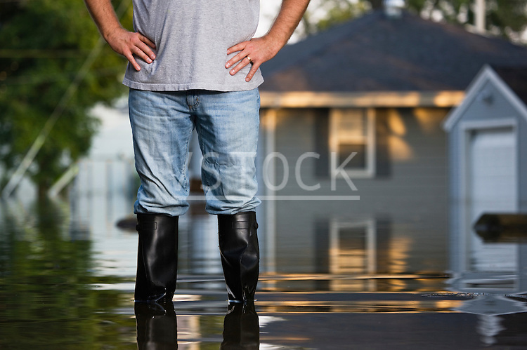 USA, Illinois, Chillicothe, Mid adult man standing in water in rubber boots, Mid section