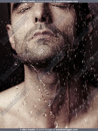 Sensual closeup portrait of a man face with closed eyes under pouring shower water