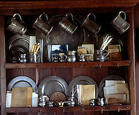 The shelves of the two-stage cupboard display a collection of pewter plates and tankards and other memorabilia