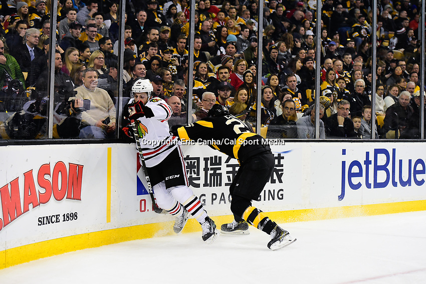 Friday, January 20, 2017: Boston Bruins defenseman Brandon Carlo (25) checks Chicago Blackhawks left wing Ryan Hartman (38) during the National Hockey League game between the Chicago Blackhawks and the Boston Bruins held at TD Garden, in Boston, Mass. Chicago defeats Boston 1-0 in regulation time. Eric Canha/CSM