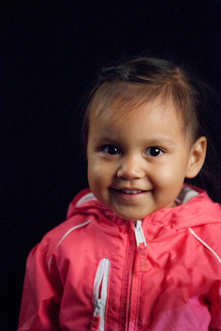 Contemporary and happy healthy Native American girl at toddler age in pink jacket next to black backdrop. Harmony Lahr (Blackfoot/Navajo)
