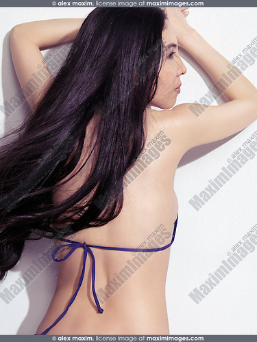 Beauty portrait of a young Japanese woman with long black hair leaning against a white wall