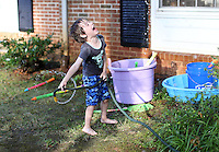 Cooper Shurtleff plays with the hose at his home in Albemarle County, VA. Photo/Andrew Shurtleff