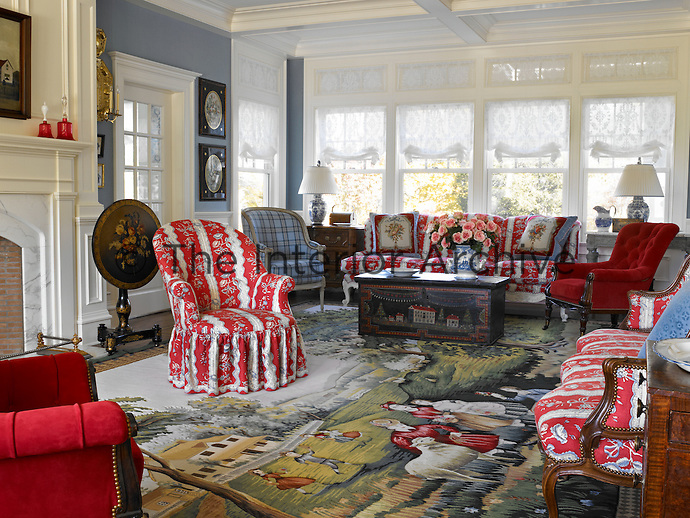 A large tapestry carpet covers the floor of the living room and is dotted with furniture covered in a variety of textiles including grey tartan, red-and-white chintz and cherry-red velvet