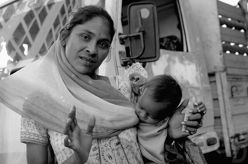 A women and child. A typical Mumbai street scene near the Bollywood area, a women beggar on the road,India