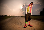 A sad clown stands on a deserted country road as the sun sets behind him..