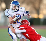 SIOUX FALLS, SD - NOVEMBER 7: Boston Bauer #12 from O'Gorman is brought down for a loss by Ned Sudbeck #7 from Lincoln in the first quarter of their Class AAA semifinal game Friday night at Howard Wood Field.  (Photo by Dave Eggen/Inertia)
