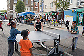 Children play table-tennis at a Tell It Parents Action Group street event to launch a drop-in advice service on the Mozart Estate, North Westminster, which has experienced problems with postcode gang violence.