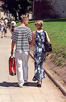 Couple age 25 walking down street arm in arm.  Krakow Poland