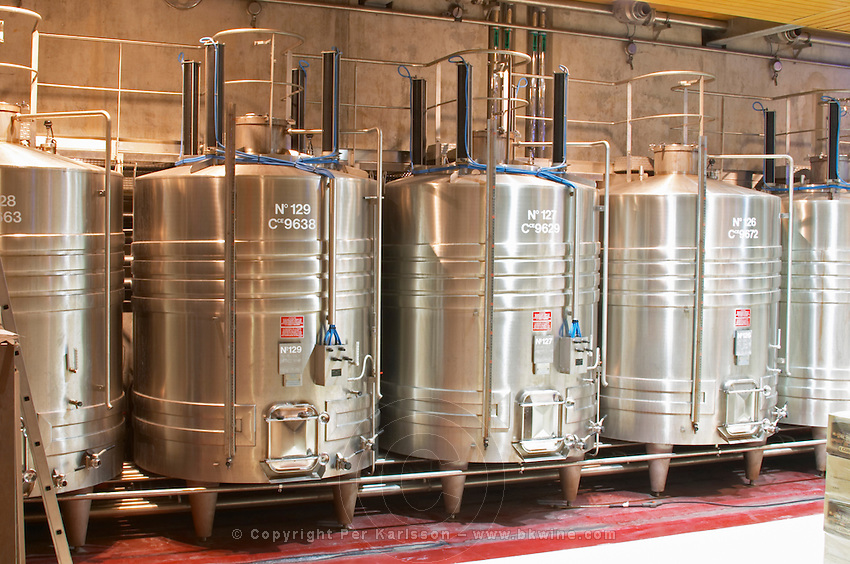 """Stainless steel fermentation tanks with on top equipment for doing """"pigeage"""". Pigeage means pushing down the """"cap"""" of grape skins and other solid material that floats to the surface down into the must to get better extraction. Traditionally done by foot or with a hand tool, now done with hydraulic equipment. Each of the four black columns is a mechanical """"foot"""".  Domaine E Guigal, Ampuis, Cote Rotie, Rhone, France, Europe"""