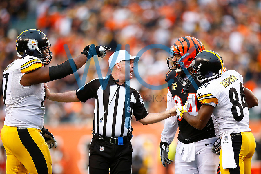 A referee gets in-between Domata Peko #94 of the Cincinnati Bengals and Marcus Gilbert #77 of the Pittsburgh Steelers in front of Antonio Brown #84 of the Pittsburgh Steelers during the game at Paul Brown Stadium on December 12, 2015 in Cincinnati, Ohio. (Photo by Jared Wickerham/DKPittsburghSports)