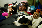Andean Mountain Cat (Leopardus jacobita) biologist, Juan Reppucci, reading with his Domestic Dog (Canis familiaris) resting on his lap, Loma Blanca, Abra Granada, Andes, northwestern Argentina