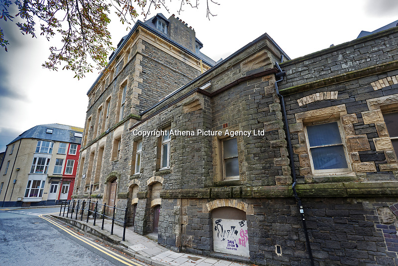 Pictured: Rear view, Queen's Road of the old Police Station in Aberystwyth, Wales, UK. Wednesday 28 August 2019<br /> Re: Opened 1866, built by the Hafod Hotel Co as the Queens Hotel; architects, Hayward and Davies; builder George Lumley of Aberystwyth. Sold in 1877 and later converted to local government use; remodelled in1950 by G R Bruce, County Architect.<br /> Detached towards N end of the Promenade, with main entrance to side elevation in Albert Place and rear elevation to Queens Road.<br /> Hotel de Ville style. Asymmetrical 3-storey attic and basement snecked rubble 13-bay W (Promenade) elevation; stepped front with mostly vermiculated dressings, stock brick voussoirs, deep entablature and cornice and cill bands; buttresses to ground floor centre. Steep pitch mansard slate roof with truncated chimney stacks. Dormers with steep overhanging roofs and casement windows; paired to left. 3-bays advanced near the right hand end and with additional storey and splayed angles to 2nd floor (with small cast-iron parapets) and 3rd floor; also to top floor) with small cast-iron parapets) and 3rd floor; also to top floor at the corner. Sash windows, some paired; anthemion panelled cast-iron window box holder across central bays.