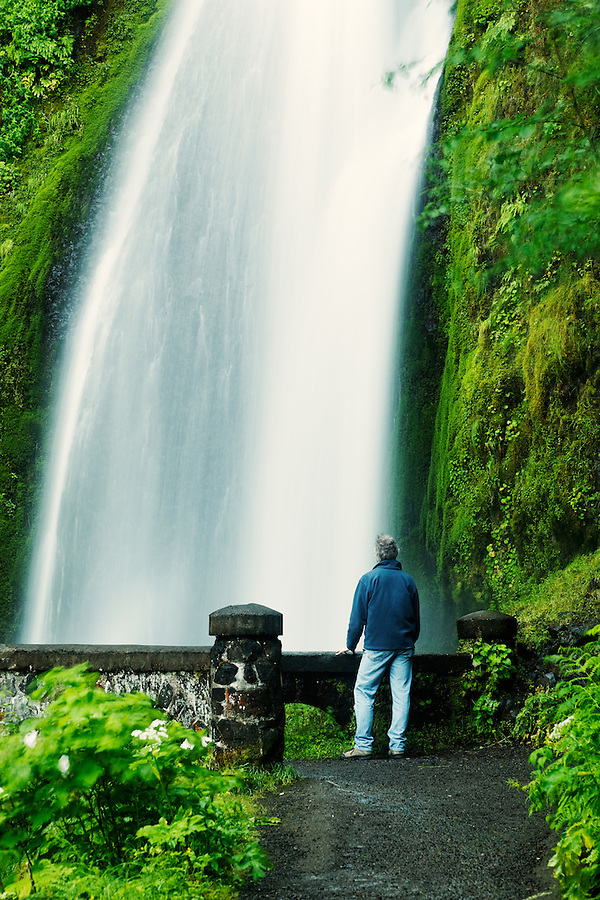 Man standing on bridge in front of Wahkeena Falls, Columbia River Gorge National Scenic Area, Oregon, USA