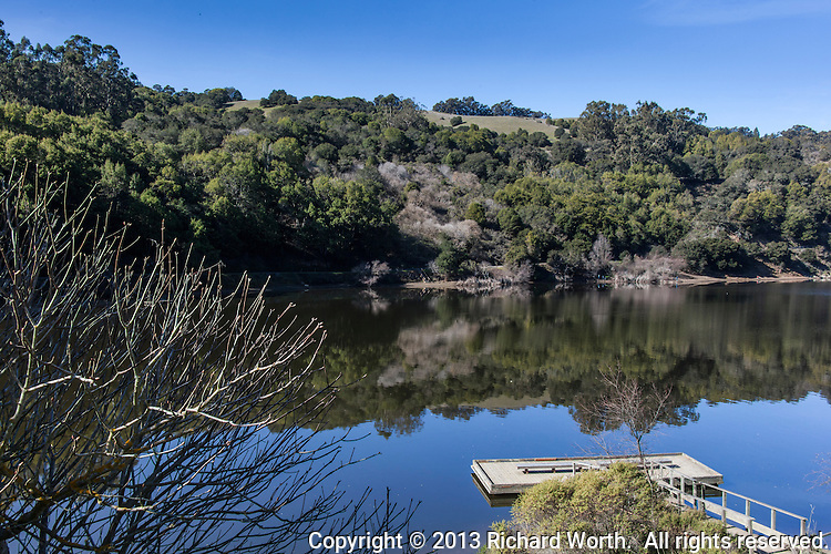 An empty fishing pier extends into a mostly calm Lake Chabot where the opposite shore lies in quiet, near perfect, reflection.