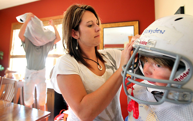 Heather Jacobs helps her sons, Brayden, 11, right, with his chin strap while Justin, 10, puts on his jersey as they prepare for a night of football before leaving with her five children for a night of activities.  Heather lost her husband, Eric, in a plane crash in 2006 when she was eight months pregnant with their youngest, Ella, and has since been raising her five young children on her own.